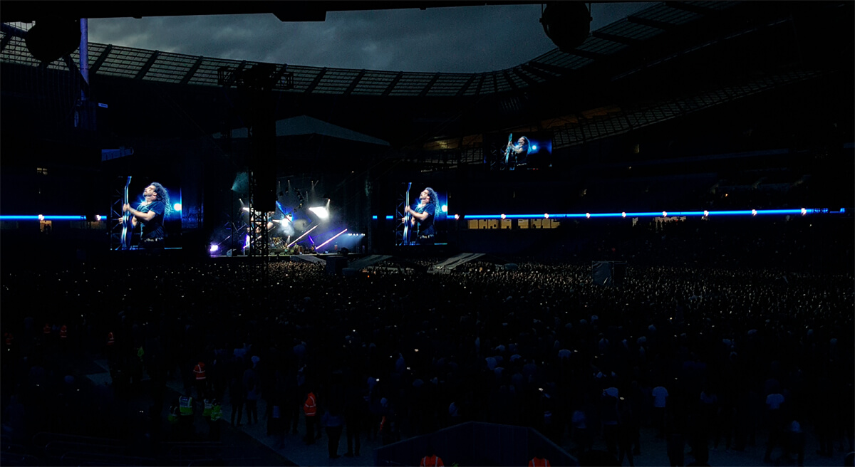 Dave Grohl holding his blue guitar up while playing it to the crowd at Etihad Stadium.