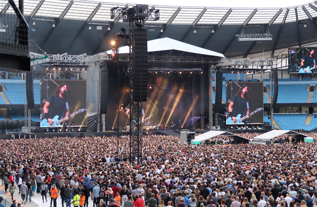 A view of the stage showing Dave Grohl playing his blue electric guitar.