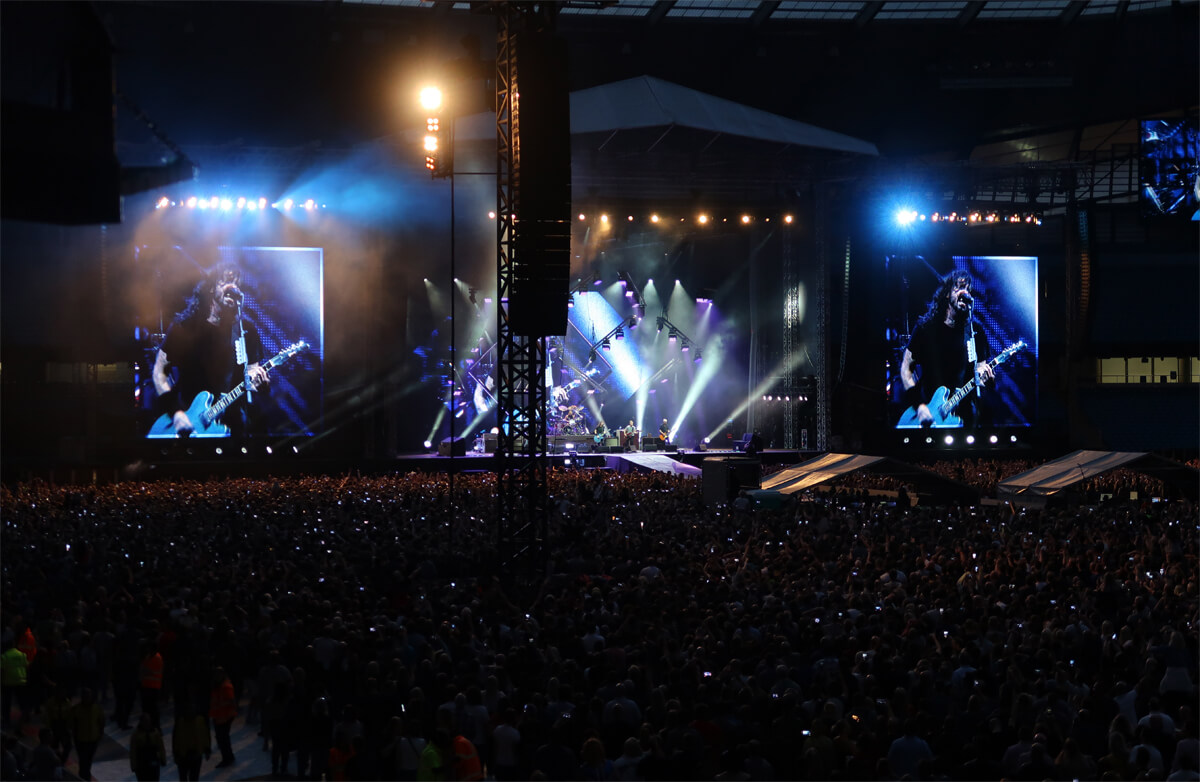 Dave Grohl singing while playing his blue guitar to the crowd at Etihad Stadium.