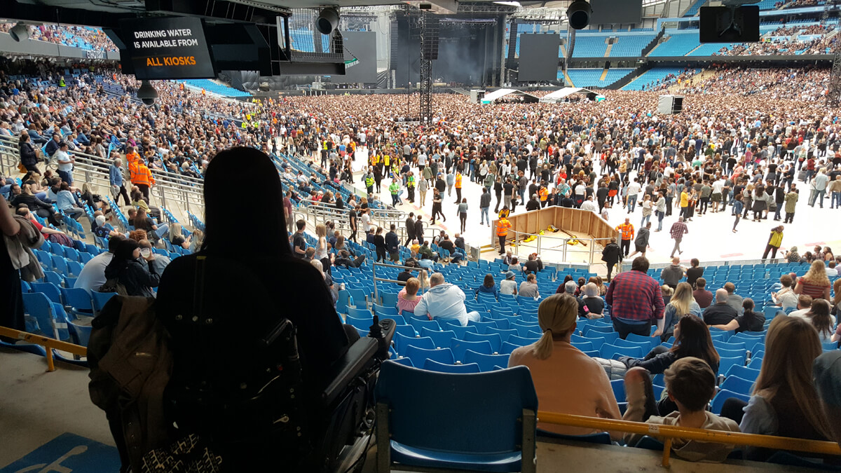 Emma sitting with her back to the camera and facing the stage. She is sitting in the accessible seating at Manchester Etihad Stadium in block 119.