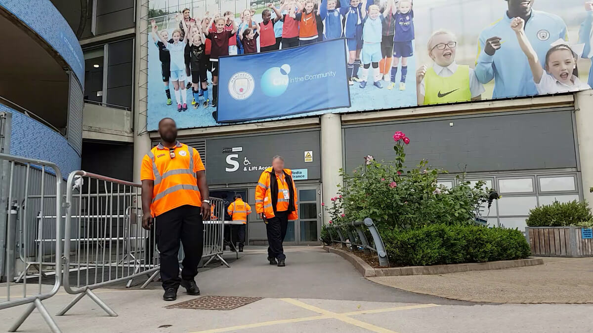 Event stewards standing at the accessible Entrance S South Stand at Manchester Etihad Stadium.