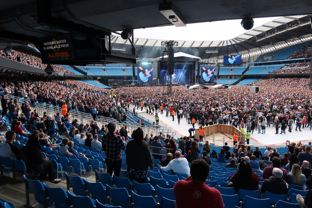 The view from the accessible seats at Manchester Etihad Stadium in block 119. The large screens show Dave Grohl playing his blue guitar.
