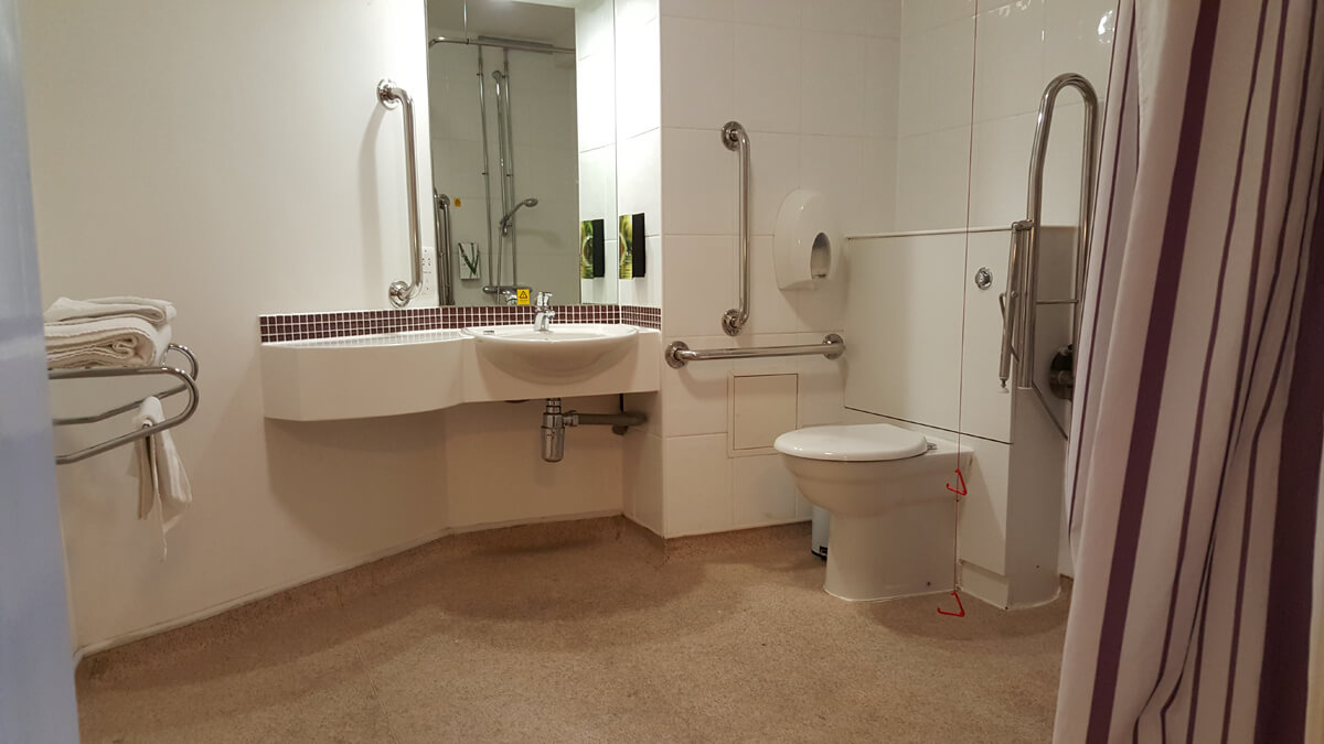 Accessible bathroom showing with a sink and toilet with an emergency pull cord next to it.