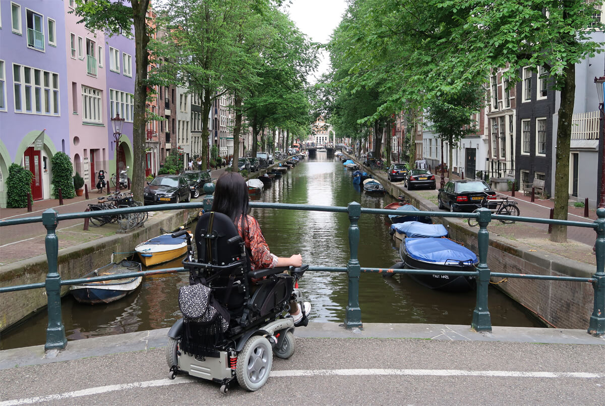 Safest Cities to Navigate With a Disability: Emma sitting in her powered wheelchair on a bridge overlooking the canal in Amsterdam.