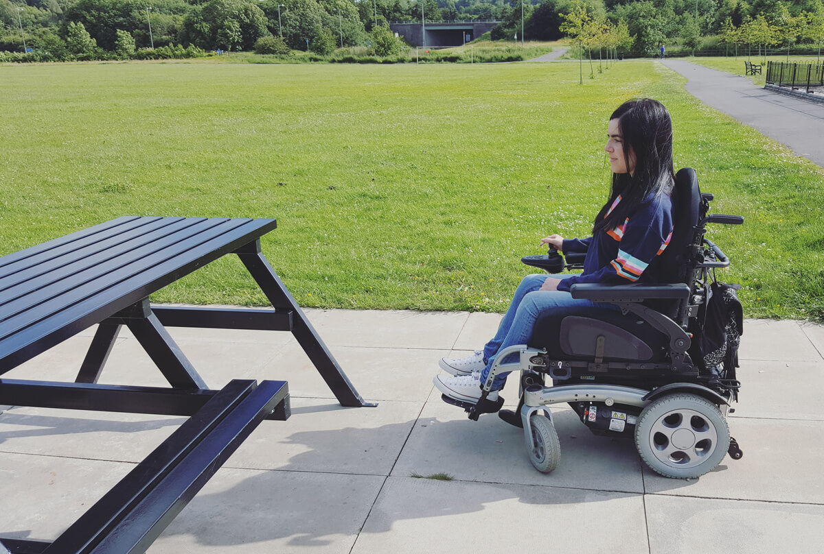 Emma sitting beside a wheelchair accessible picnic table in a sunny park.