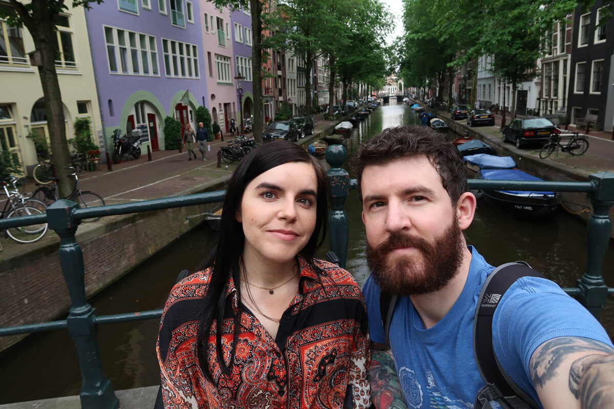 Things I've Loved in June: Emma and Allan smiling together beside a canal in Amsterdam. Emma is wearing a paisley pattern shirt and Allan is wearing a blue t-shirt.