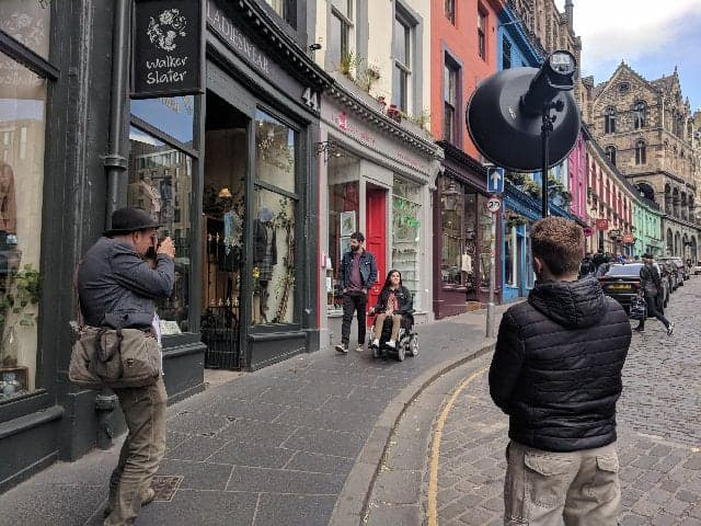 Things I've Loved in June: A behind the scenes photo of Emma and Allan during their photoshoot with VisitScotland. The photo shows Emma in her wheelchair and Allan on Victoria Street in Edinburgh with the photographer and lighting technician.