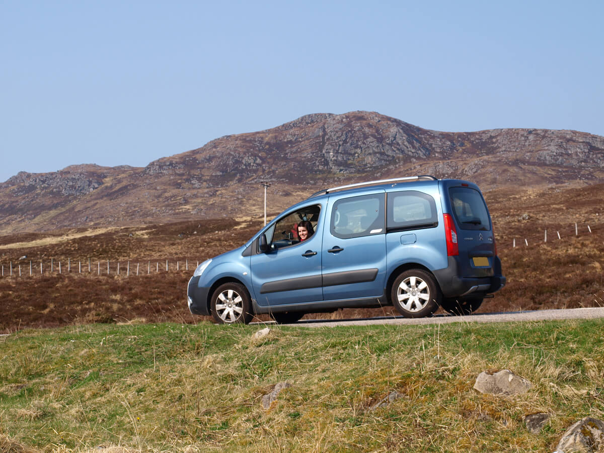 A wheelchair accessible vehicle (Citreon Berlingo) with the Scottish mountains in the background.