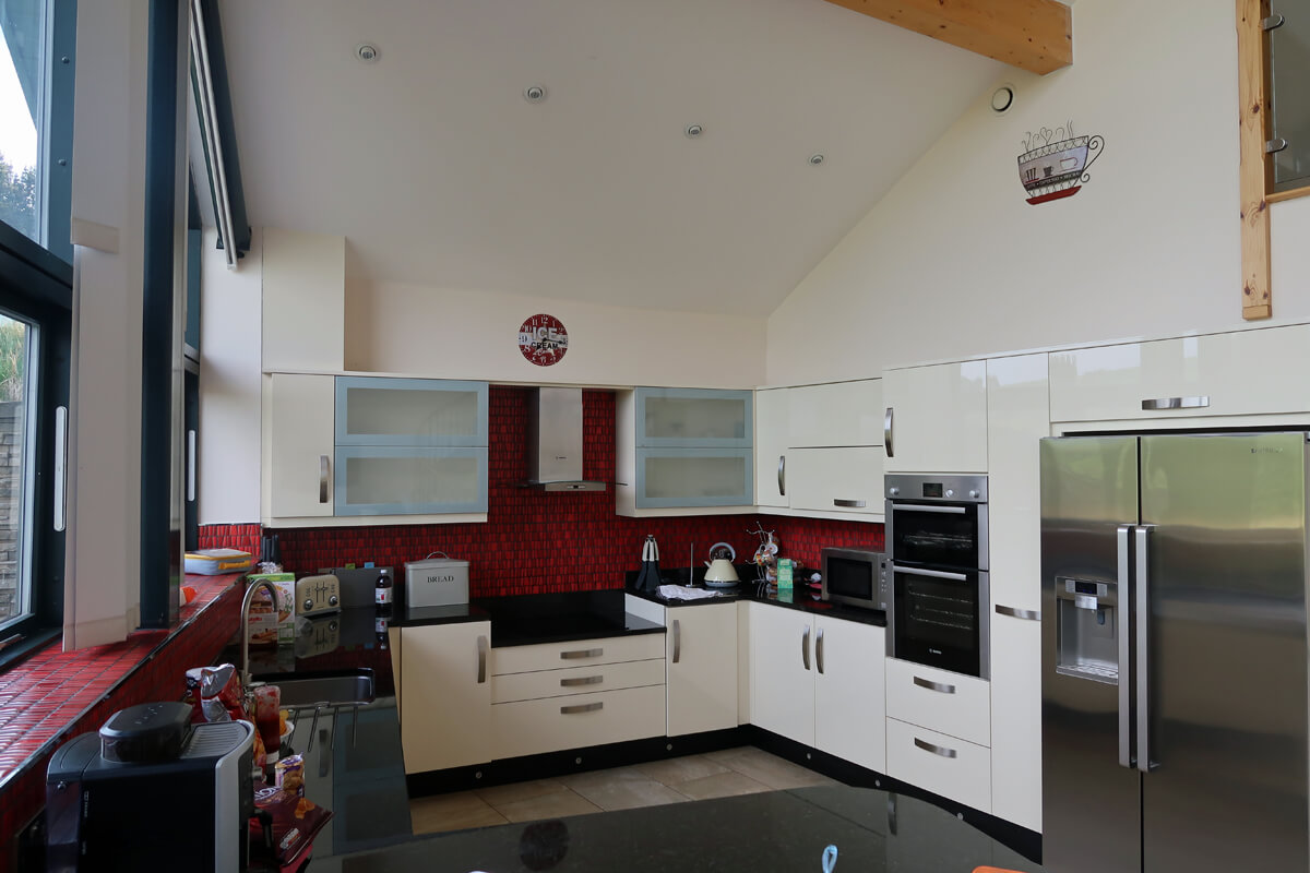 The kitchen with red tiled walls, black worktops and white cabinets.