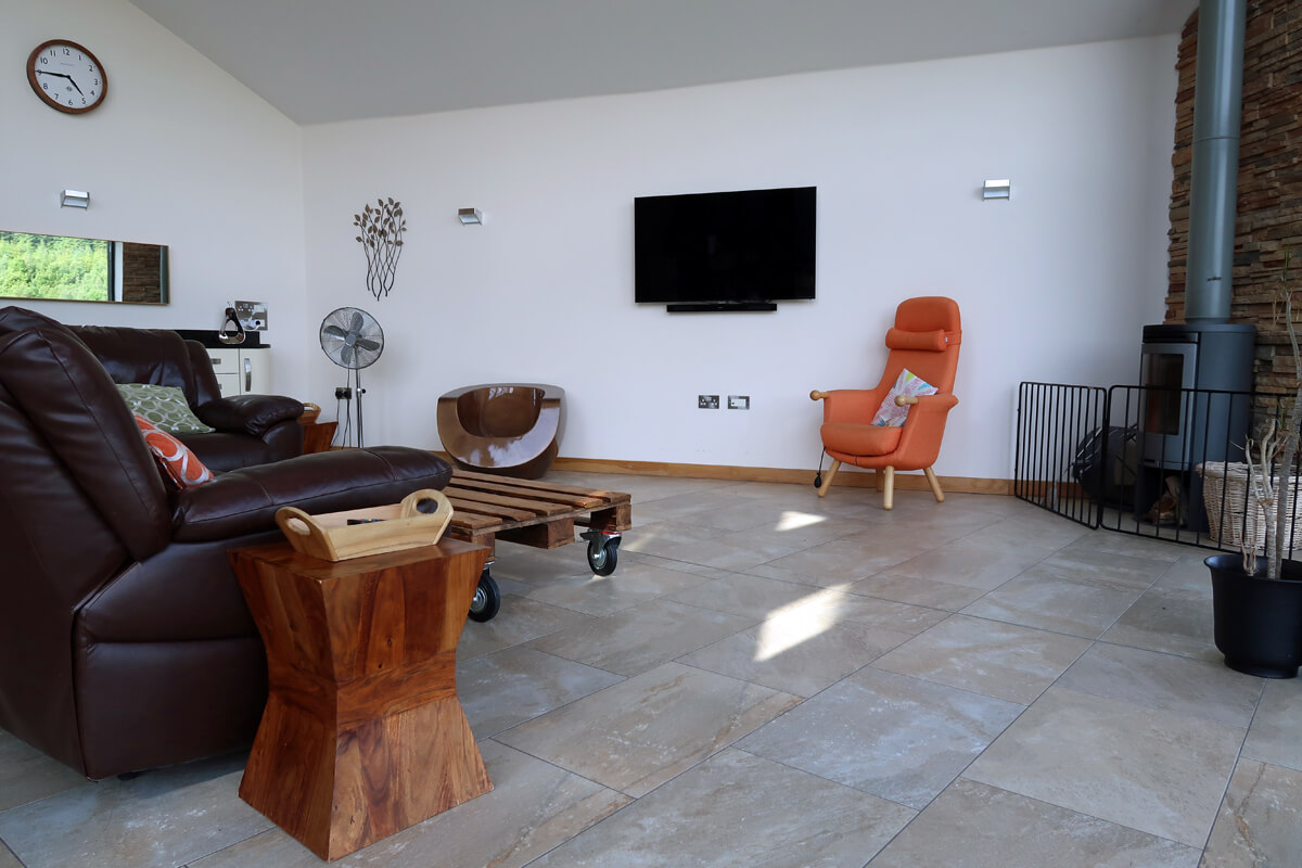The lounge with a large flatscreen TV on the wall and a woodburning stove in the corner