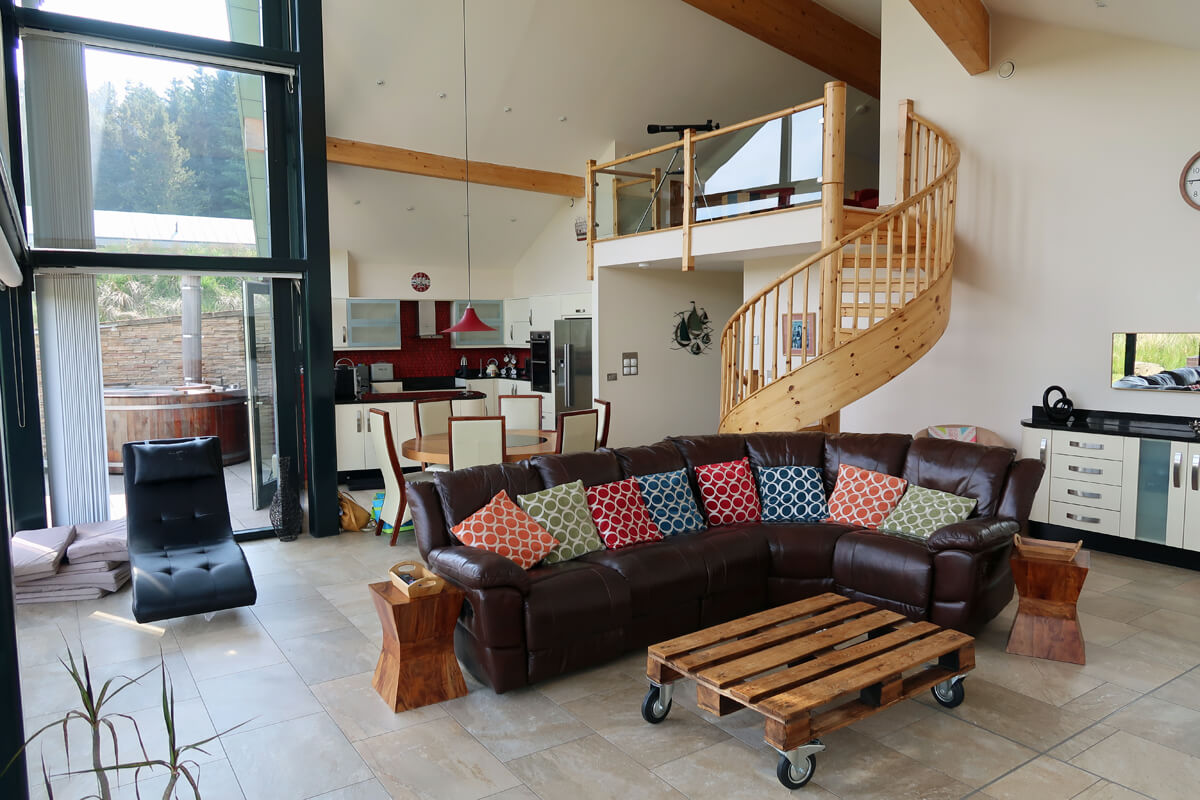 The L shaped sofa with different coloured cushions. A spiral staircase is behind the sofa and also shows the open plan kitchen and dining area.