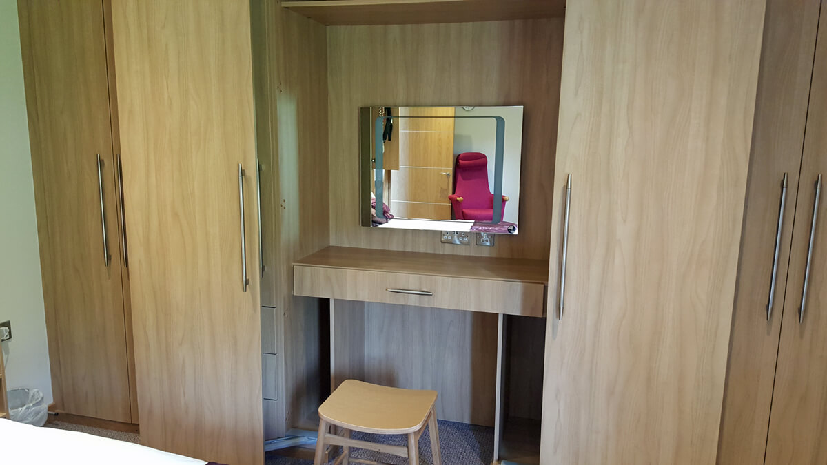 A vanity table and light up mirror inside the wardrobe.