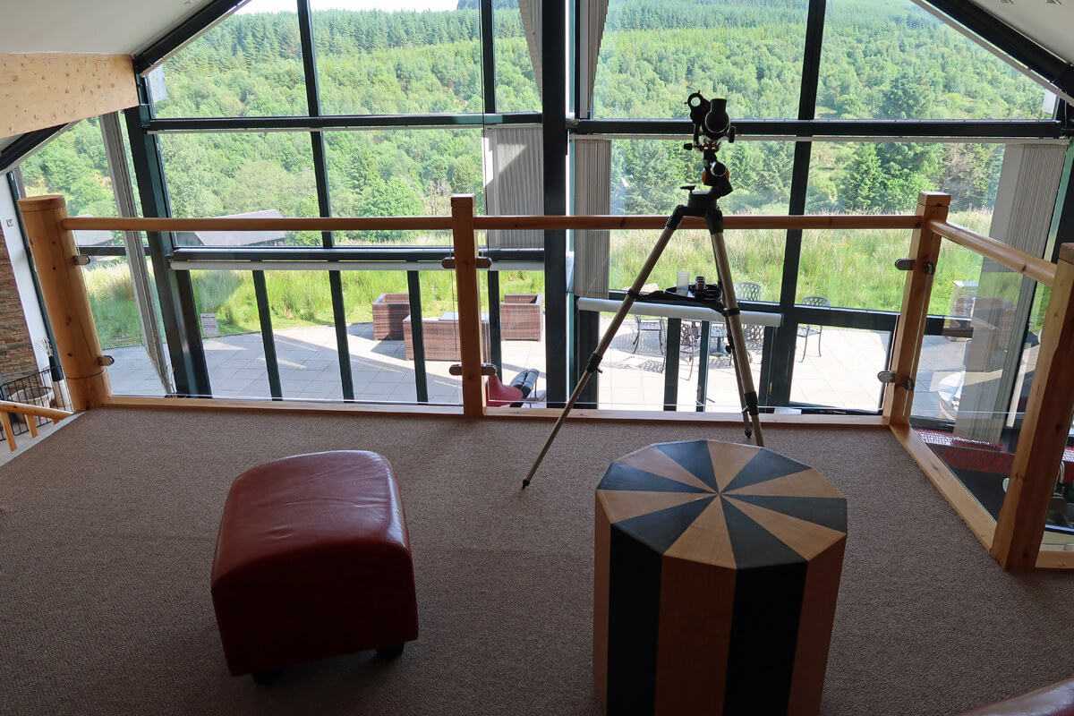 A view from the upstairs mezzanine with seating and the telescope.