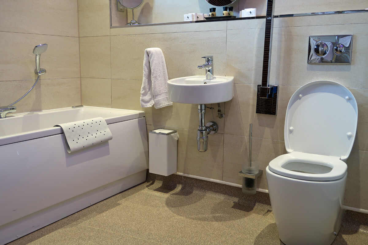 The bath, sink and toilet with grab bars in the second bathroom