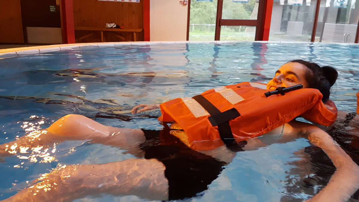 Emma wearing a life jacket while lying on her back in the hydrotherapy pool.