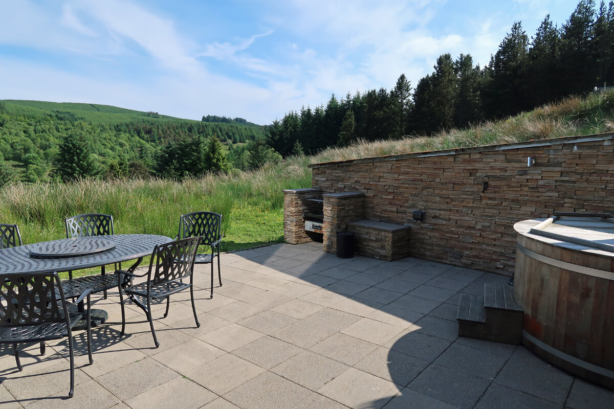 The patio terrace with eco friendly woodburning hot tub, barbecue and table.