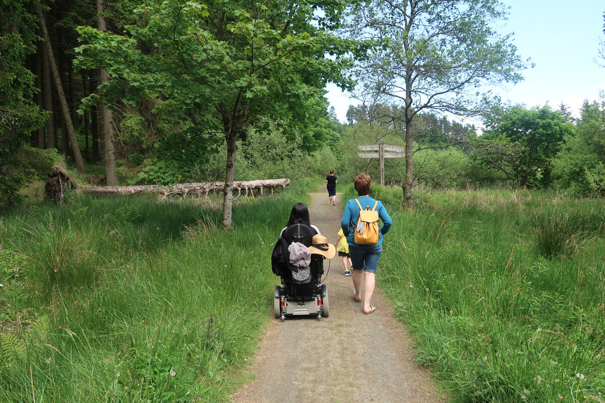 Emma and her family enjoying an accessible walk through an forest nature trail.