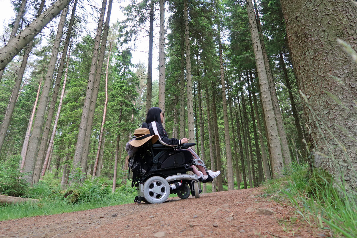 Emma sitting in her powered wheelchair driving up a sloped path in the forest.