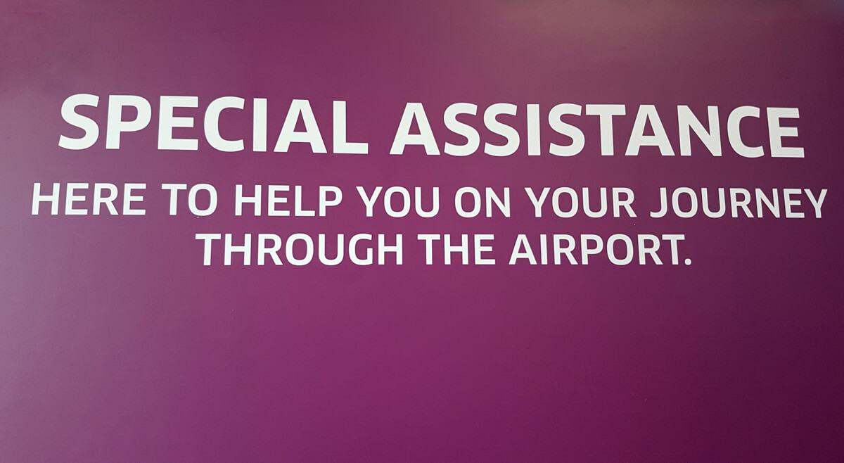 "A sign in the special assistance office with the words ""Special Assistance. Here to help you on your journey through the airport""."