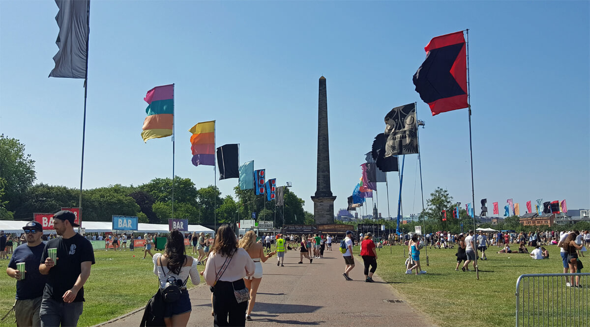 The Nelson Monument in Glasgow Green with colourful festival flags lining the accessible pathway.
