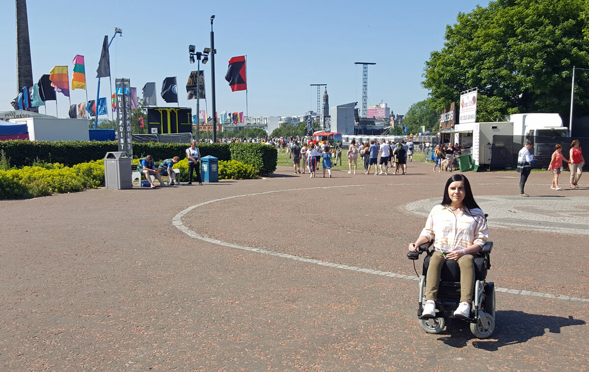 Emma sitting in her wheelchair inside the entrance of the festival. The main festival grounds were behind Emma.