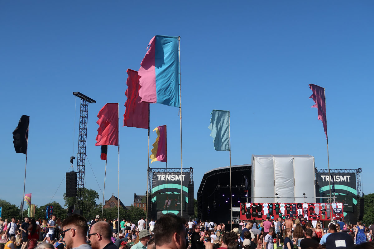 A variety of colourful festival flags blowing gently in the wind. A clear blue sky and the TRNSMT main stage in the background.