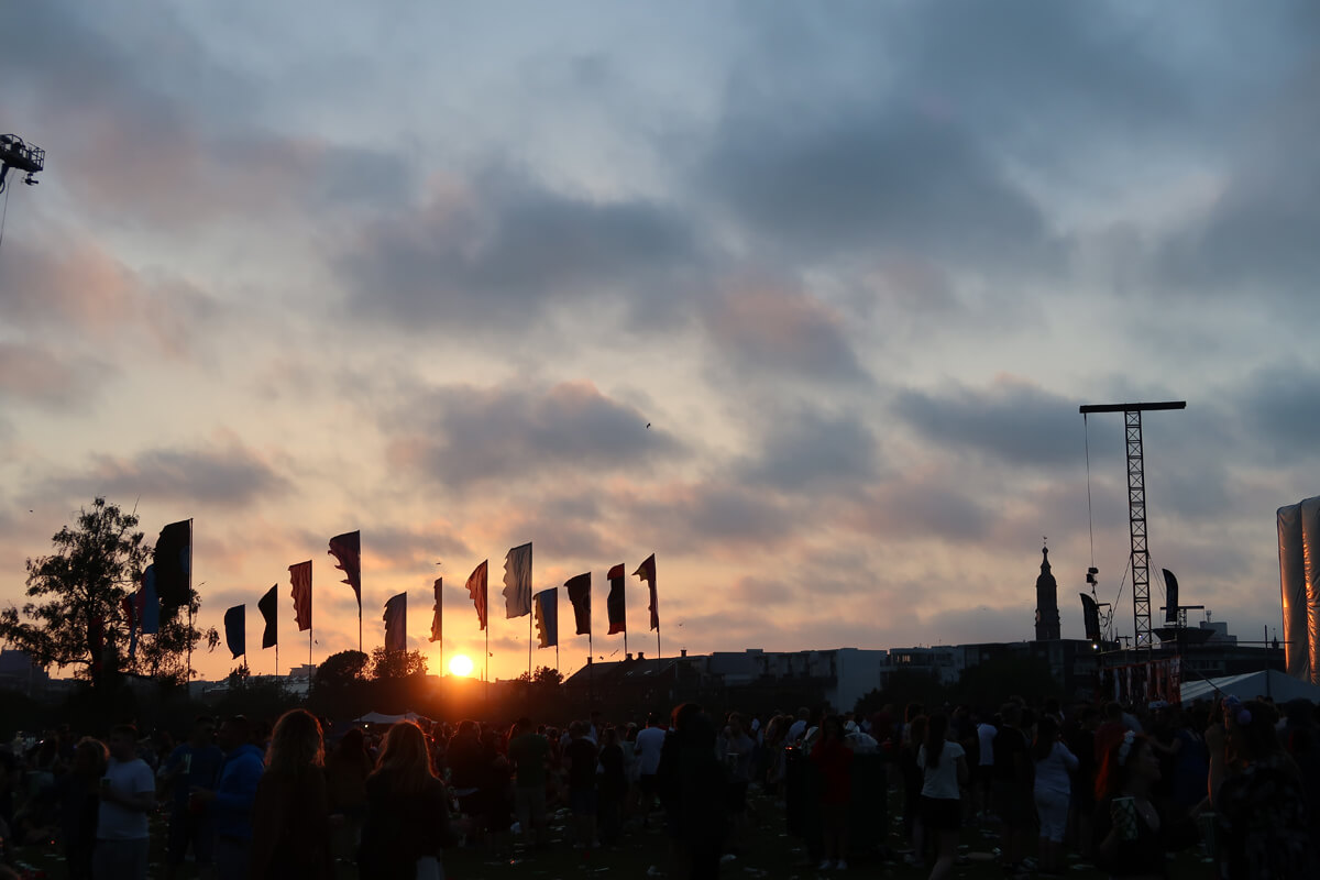 A sunset sky with a silhouettes of festival flags.