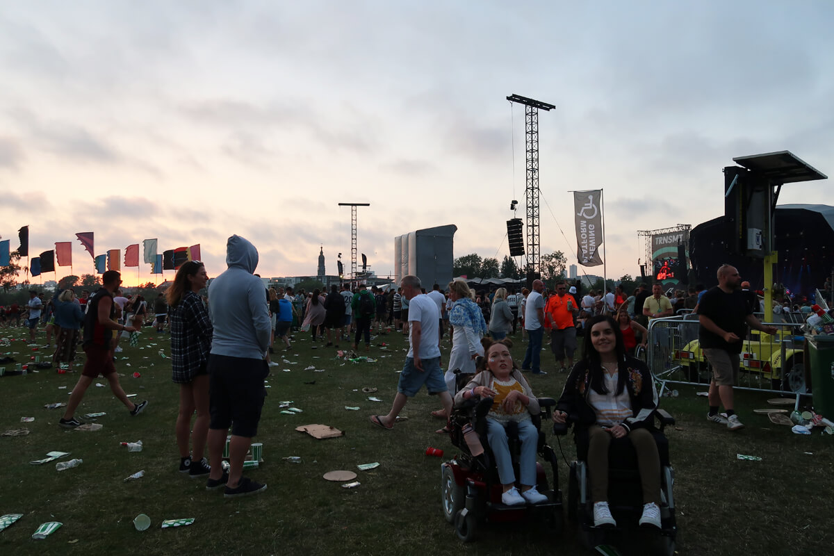 Emma and Claire D'All both in their powerchairs with the TRNSMT main stage in te background while Stereophonics perform.