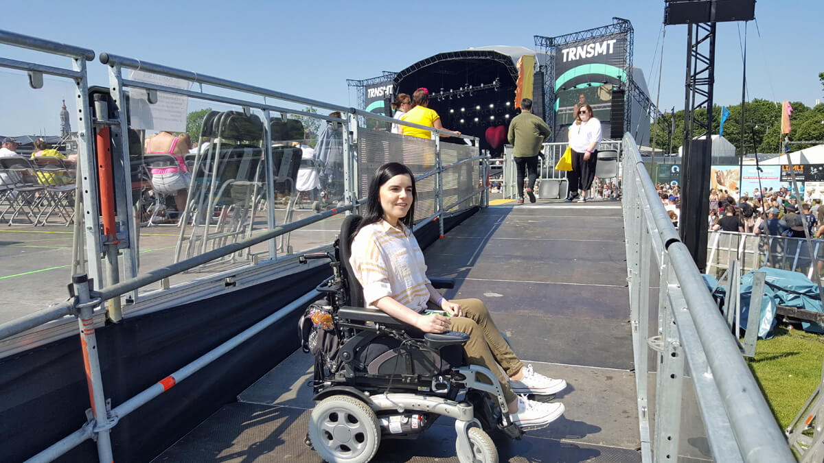 Emma sitting in her wheelchair on the ramp leading up to the Main Stage accessible viewing platform.