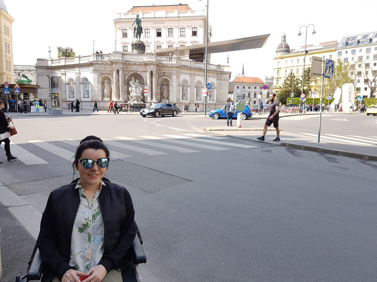 Emma sitting in her wheelchair with the Albertina Museum behind her.