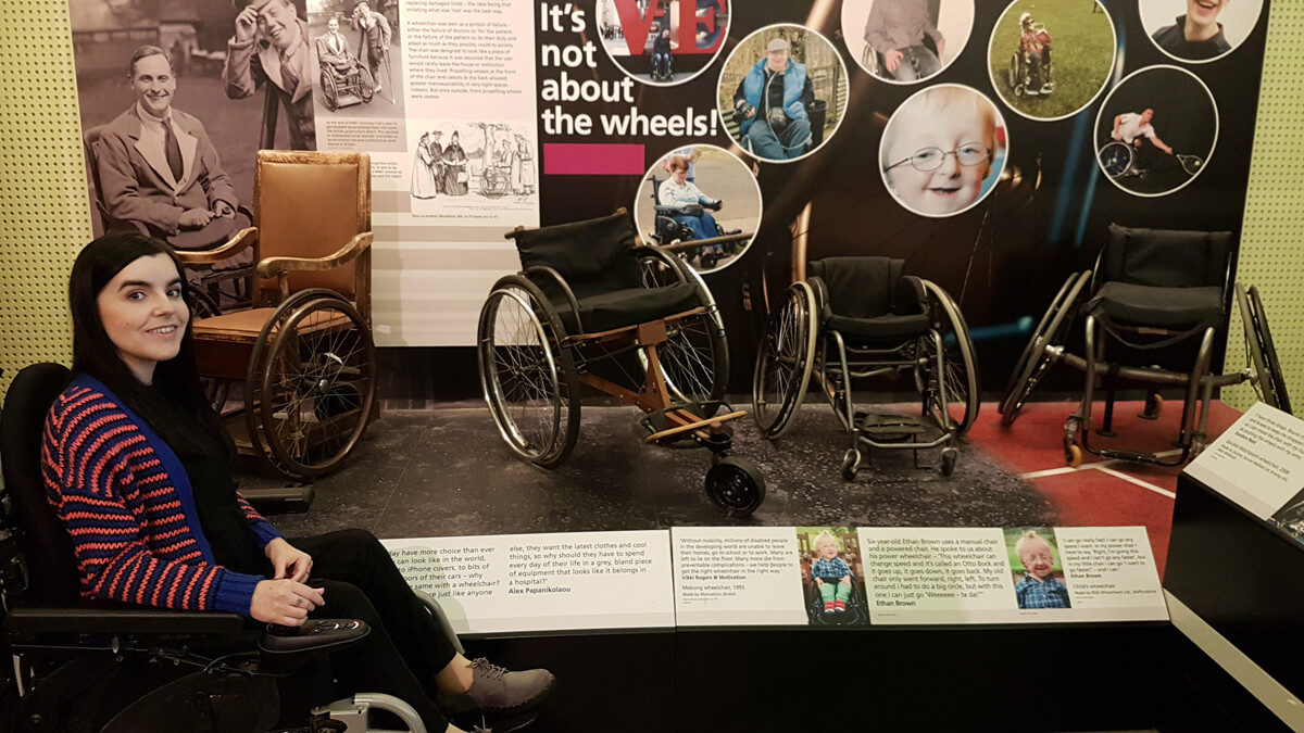 Emma sitting in her wheelchair next to a display of wheelchairs from throughout history at Riverside Museum.