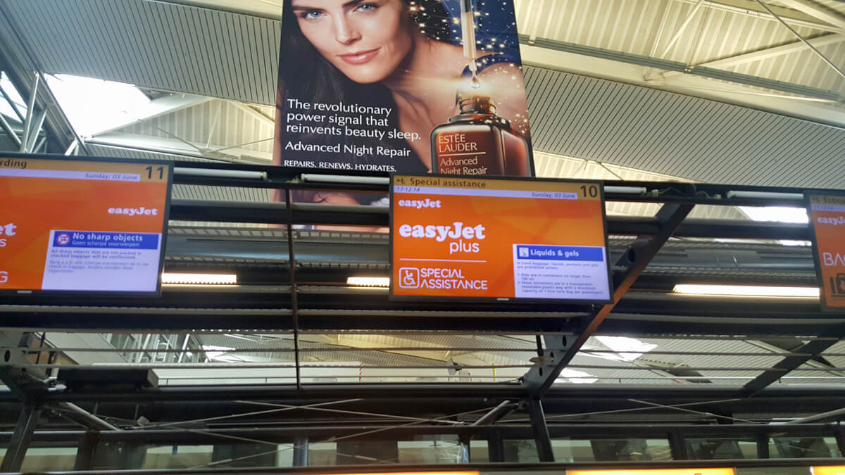 EasyJey check-in desks at Amsterdam Airport. One desk has a screen above showing that it is a special assistance easyJet check-in desk.