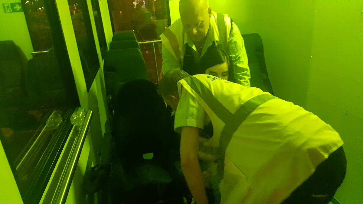 Emma being transferred from an aisle chair to her wheelchair inside the ambulift truck by two special assistance agents.