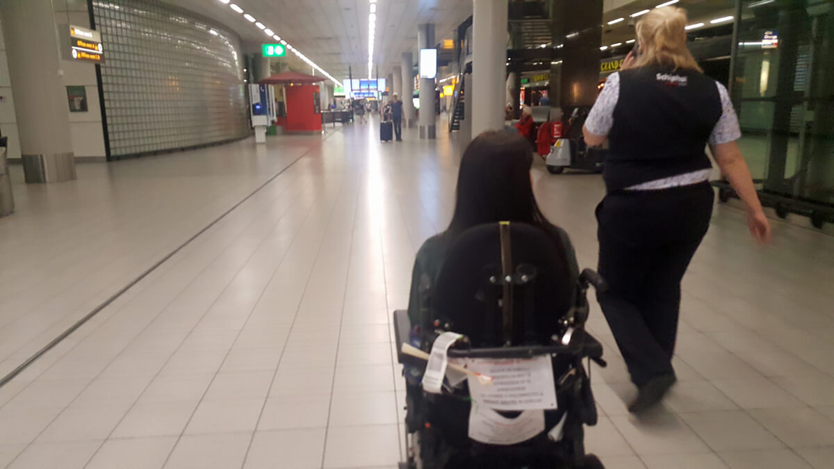 Emma being escorted through Amsterdam Airport Schiphol by a special assistance agent.