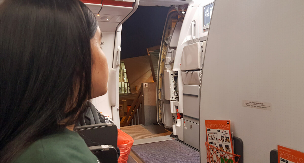 Emma sitting in the front row on an easyJet plane. The plane door is open, all passengers have disembarked but Emma is waiting on special assistance to arrive to help her off the plane.