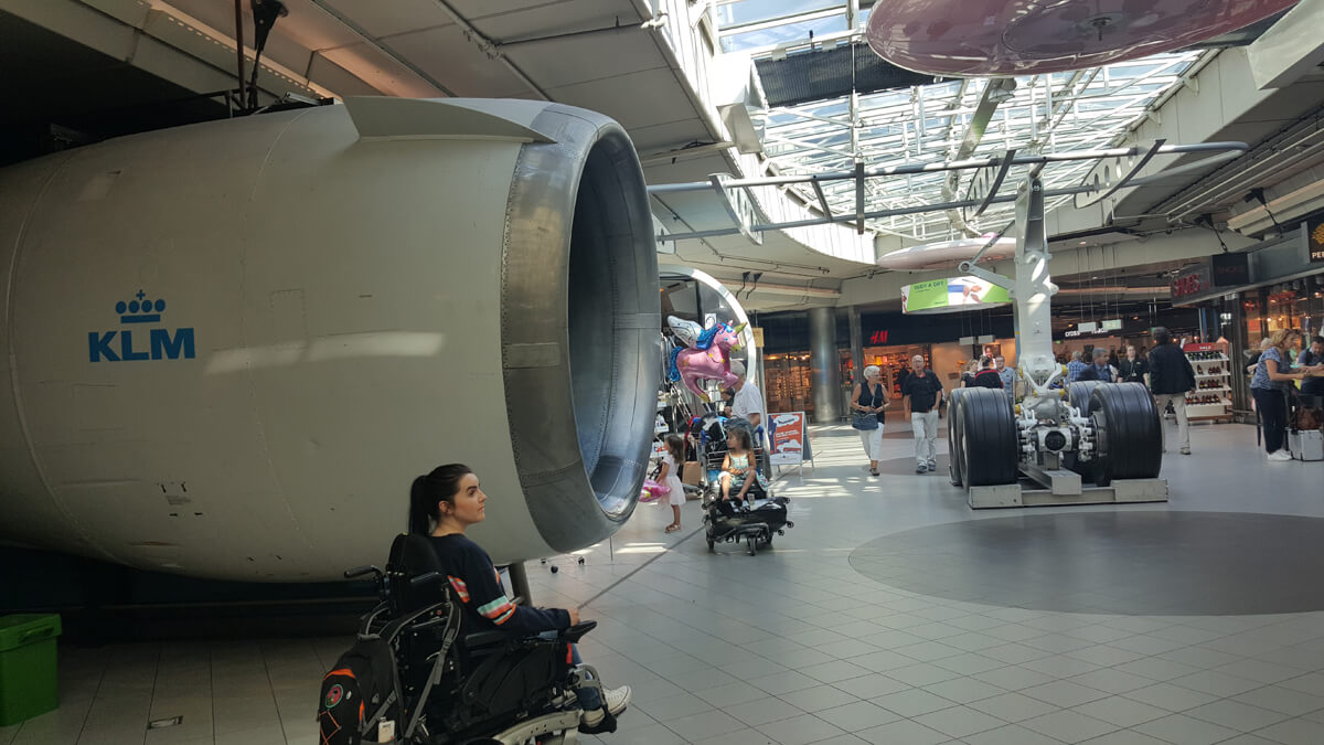 Emma sitting in her wheelchair at Amsterdam airport beside a jet engine from a KML aircraft.