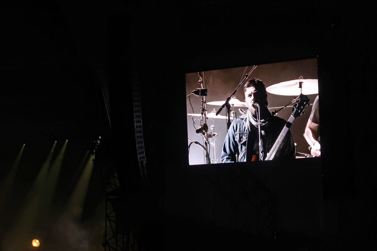 Caleb playing guitar on the big screens behind the stage at Glasgow Summer Sessions.