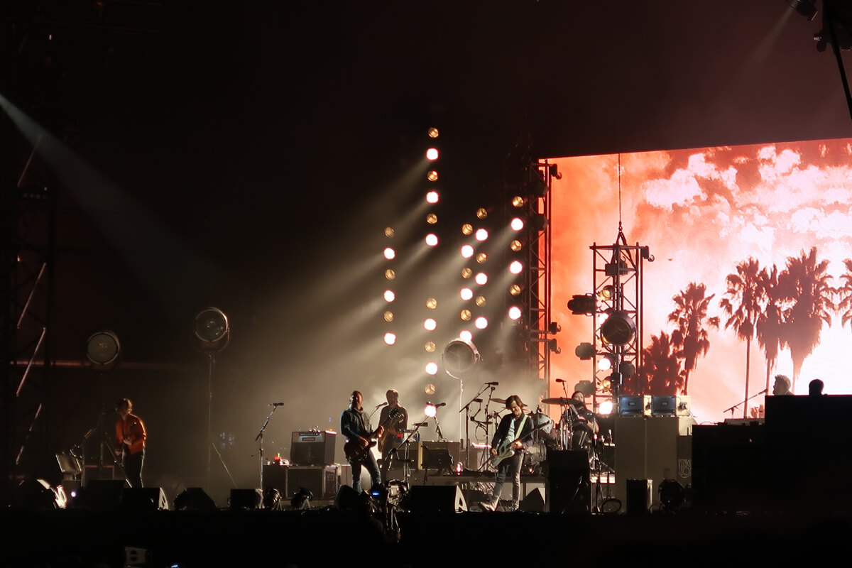 Kings of Leon playing on stage while palm trees are shown on the screen behind them.