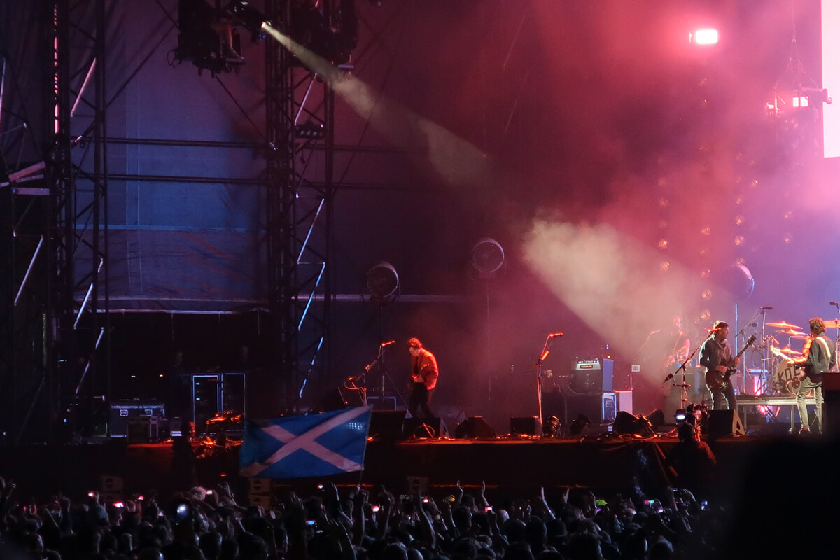 A Scottish flag waving in the crowd while Kings of Leon perform on stage.