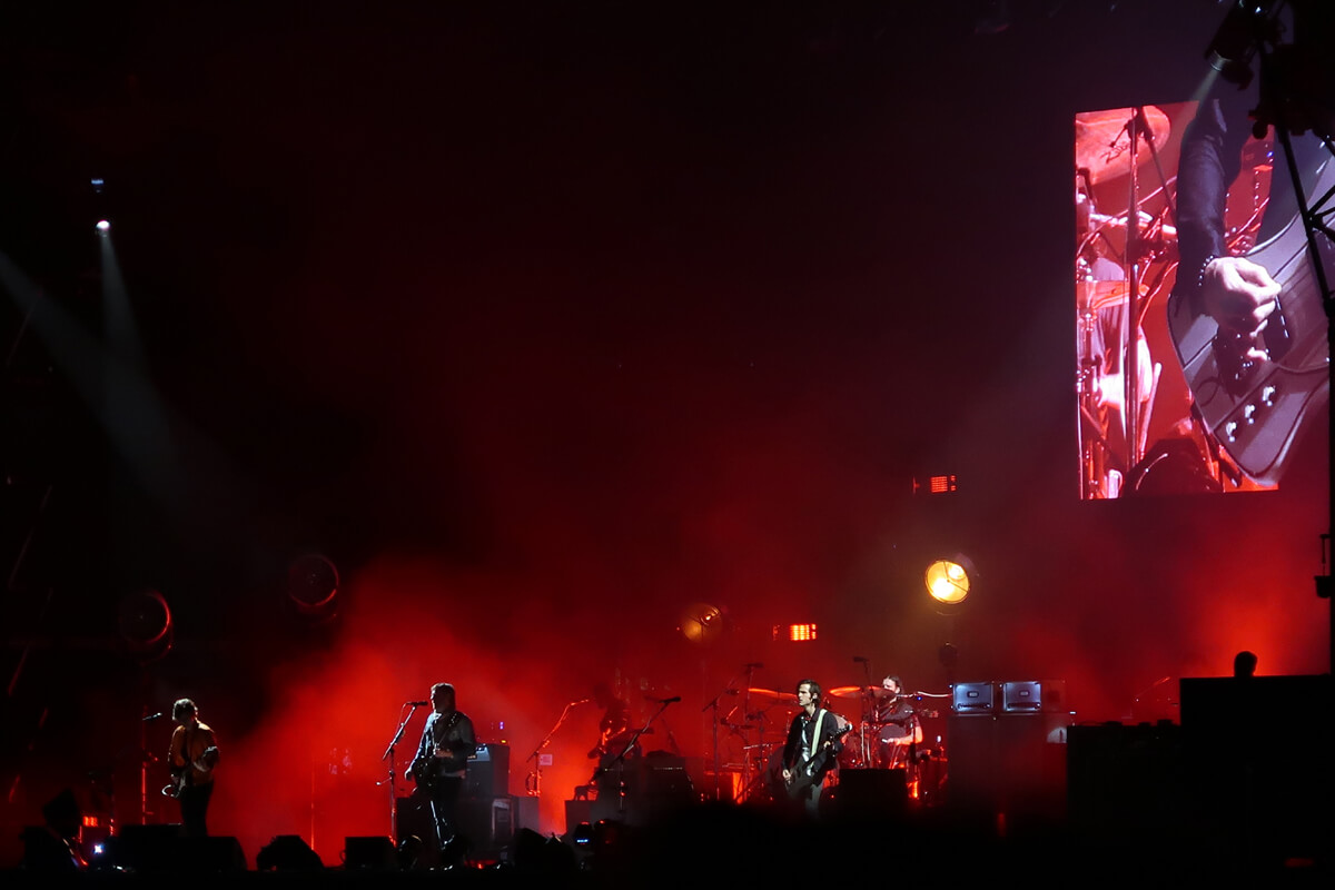 The stage is cast in red lights while Kings of Leon perform on stage.