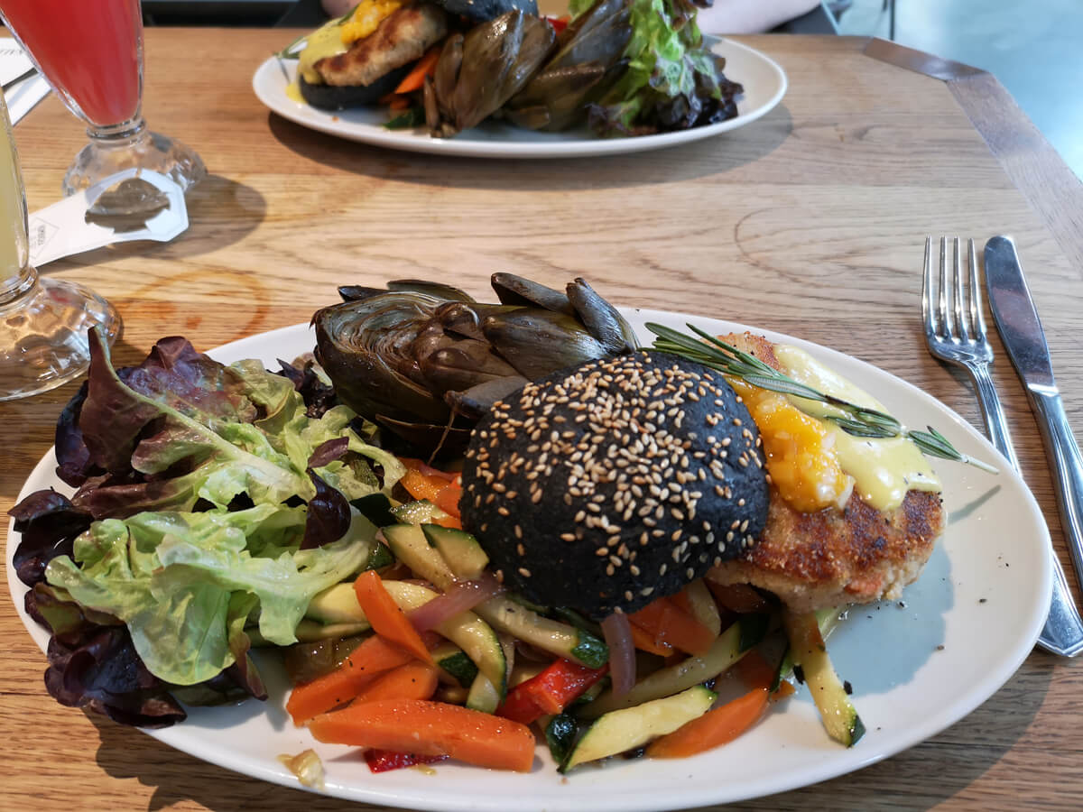 A close up of a plate with a vegan burger, salad and vegetables in Flax & Kale restaurant in Barcelona.