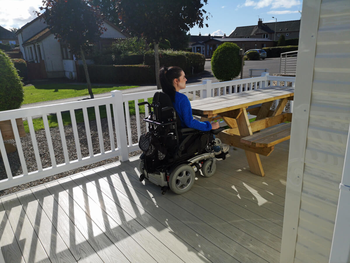 Emma sitting in her powered wheelchair at the accessible picnic table on the outside decking.