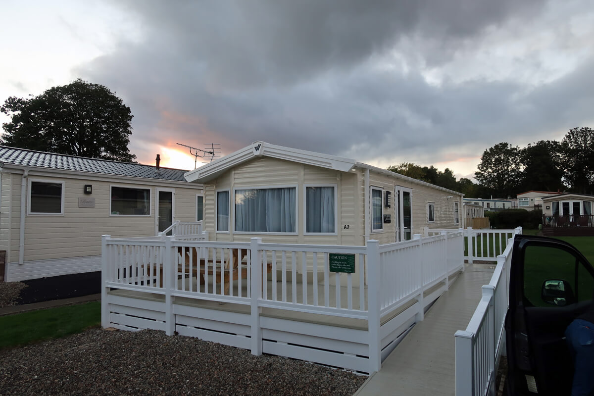 Our wheelchair accessible caravan with a few caravans in the background and a sunset.