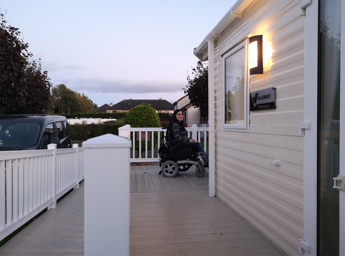 Emma sitting in her wheelchair on the outside decking of the caravan. The sun has set and the sky is a dusty pink/purple colour. Emma is wearing a grey and white stripe sweatshirt.