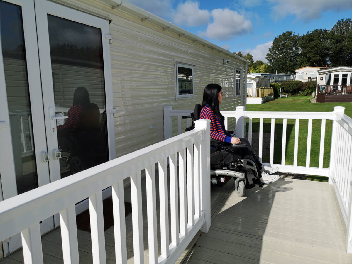 Emma sitting outside on the decking beside the caravan door. Emma is looking across to the other caravans. She is wearing a blue and orange striped cardigan, black skinny jeans and white converse shoes.