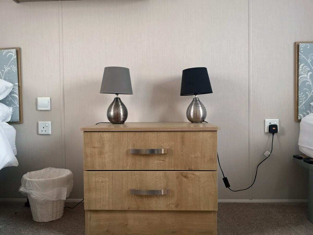 A chest of drawers placed inbetween the twin beds. There is power sockets beside each bed and one has a USB socket.