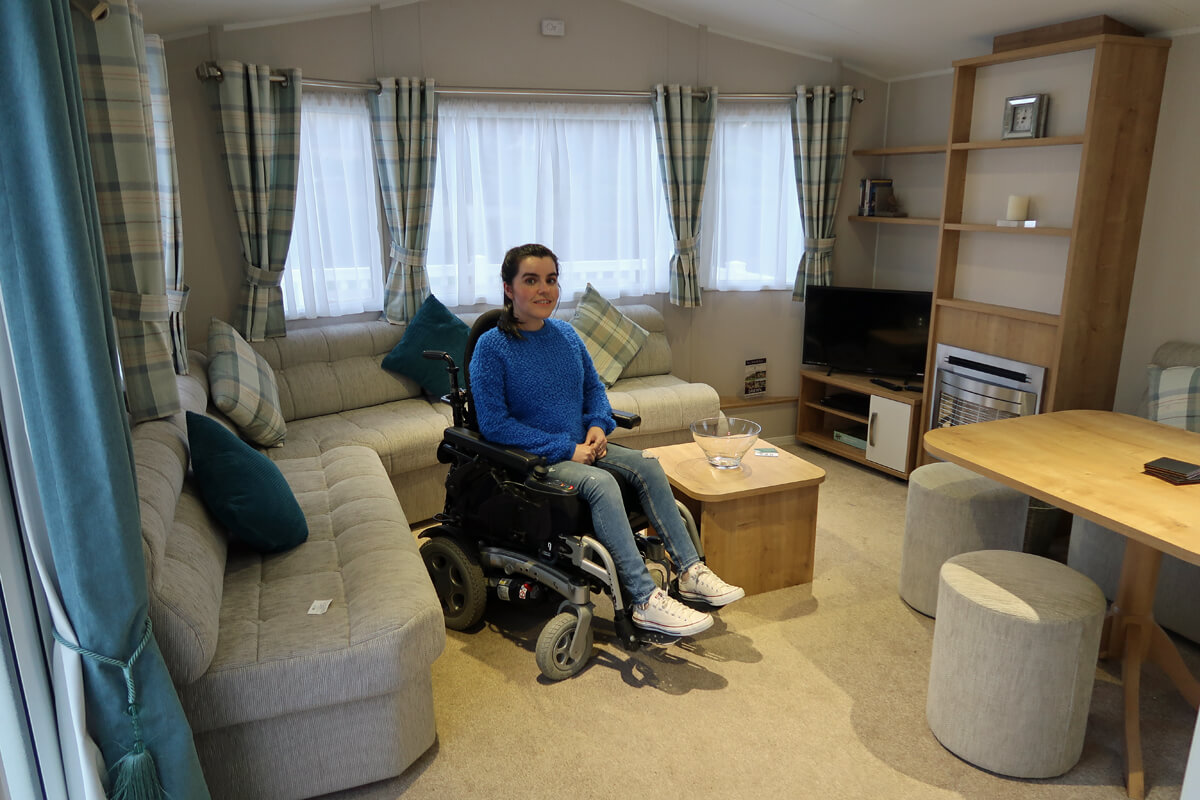 Emma sitting in her powered wheelchair in the middle of the caravan livingroom.