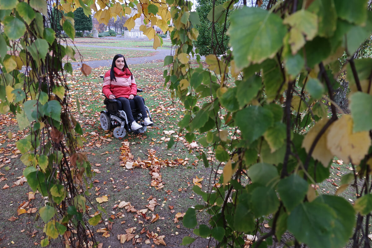 Emma is in her local park. She is sitting beside a giant number four shaped out of leaves and surrounded by trees. All the leaves are autumnal.