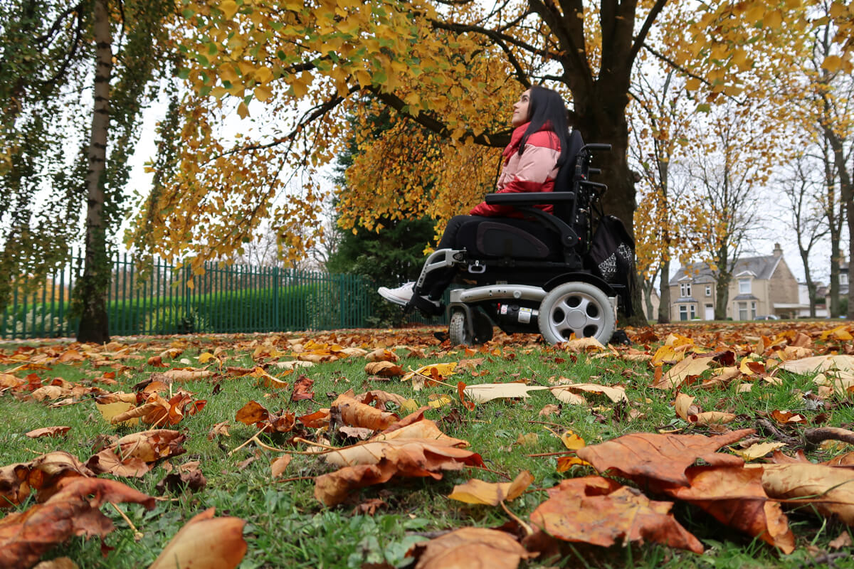 A shot looking up at Emma sitting in her wheelchair. There are leaves on the grass and beautiful autumnal trees.