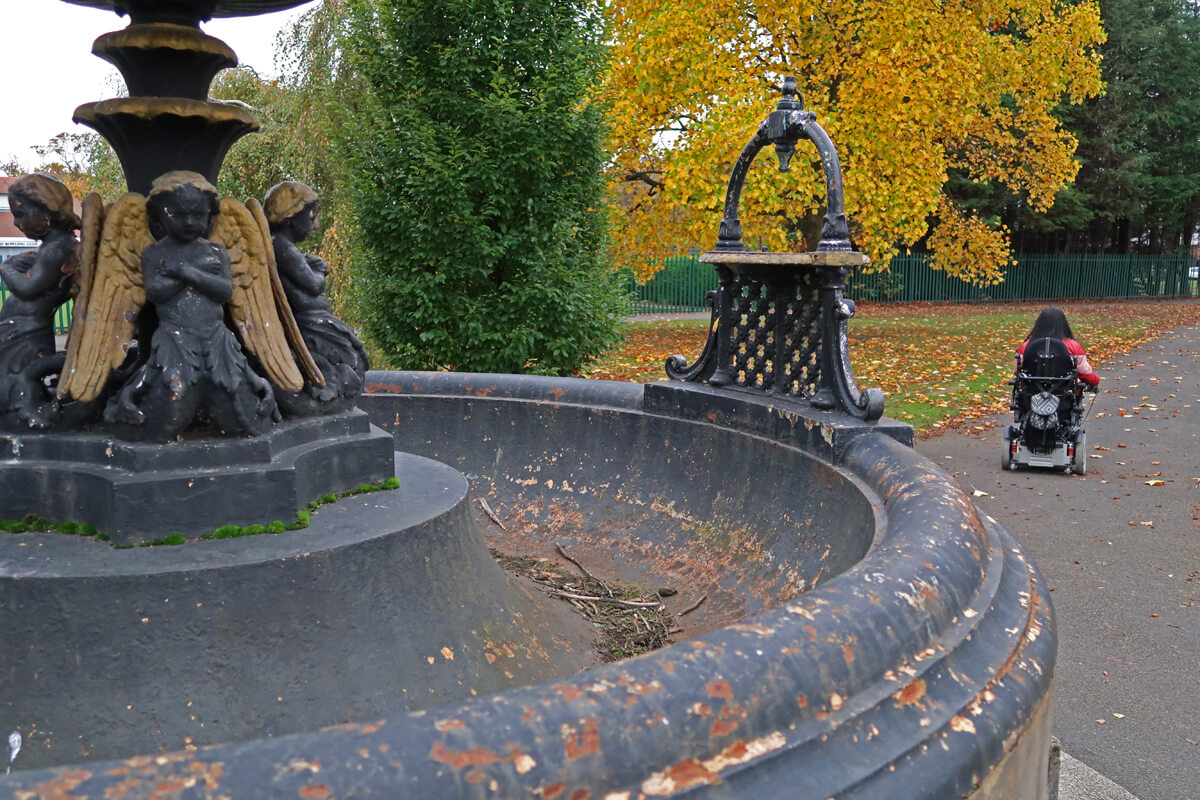 A close up of an old fountain in a park with Emma driving her powered wheelchair in the background.
